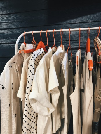 Image of a clothing rack with white clothes hanging from it.