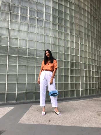 Image of a woman wearing an orange top and white pants.